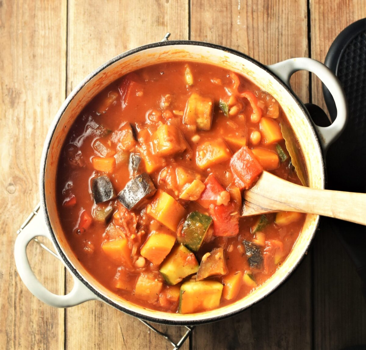 Chunky vegetable stew in tomato sauce in large white post with wooden spoon.