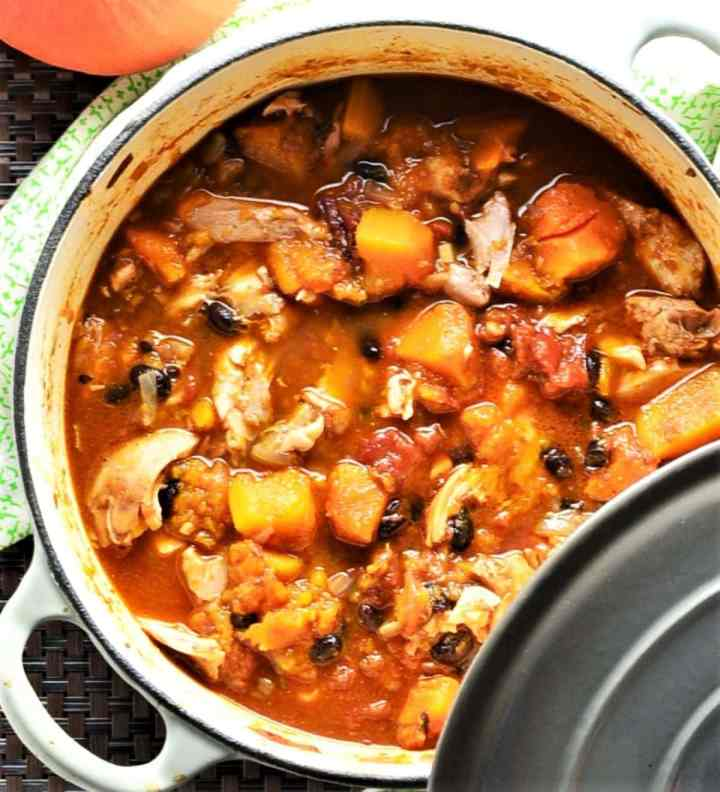Top down view of chicken and squash casserole in large pot with lid.