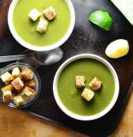 Top down view of split pea soup in 2 white bowls with croutons, lime wedges, spoons and dish of croutons on oven tray.