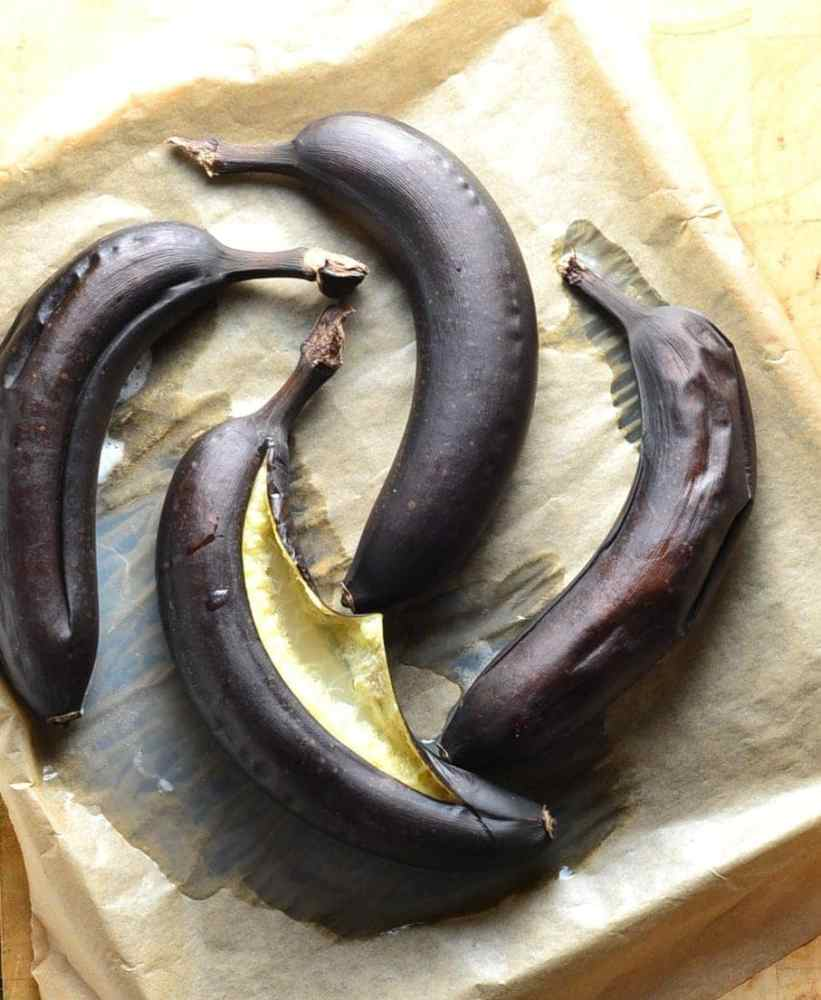 Top down view of 4 baked bananas on oven tray lined with baking paper.