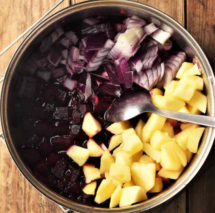 Cubed beets, apple, chopped red onion with spoon in pot.