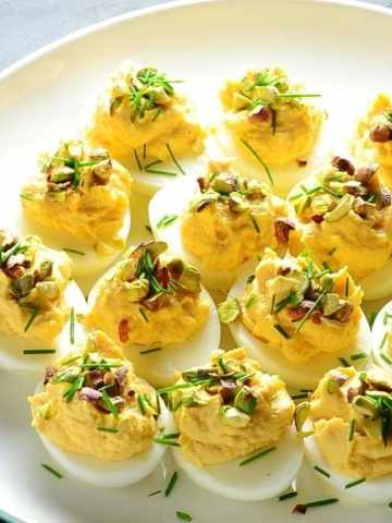 Smoked salmon deviled eggs with garnish of pistachios and chives on white plate.