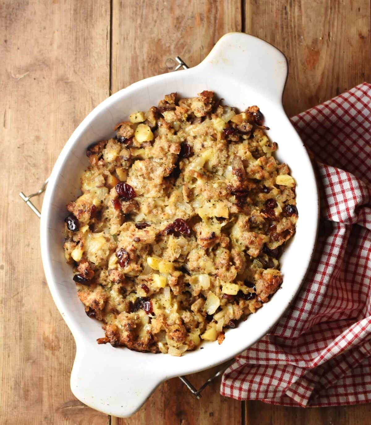 Top down view of baked vegetarian stuffing in white oval dish with red-and-white checkered cloth to the right.
