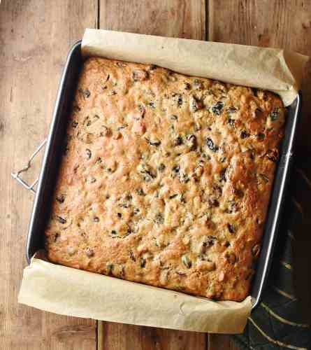 Top down view of baked fruit cake in square pan lined with paper.