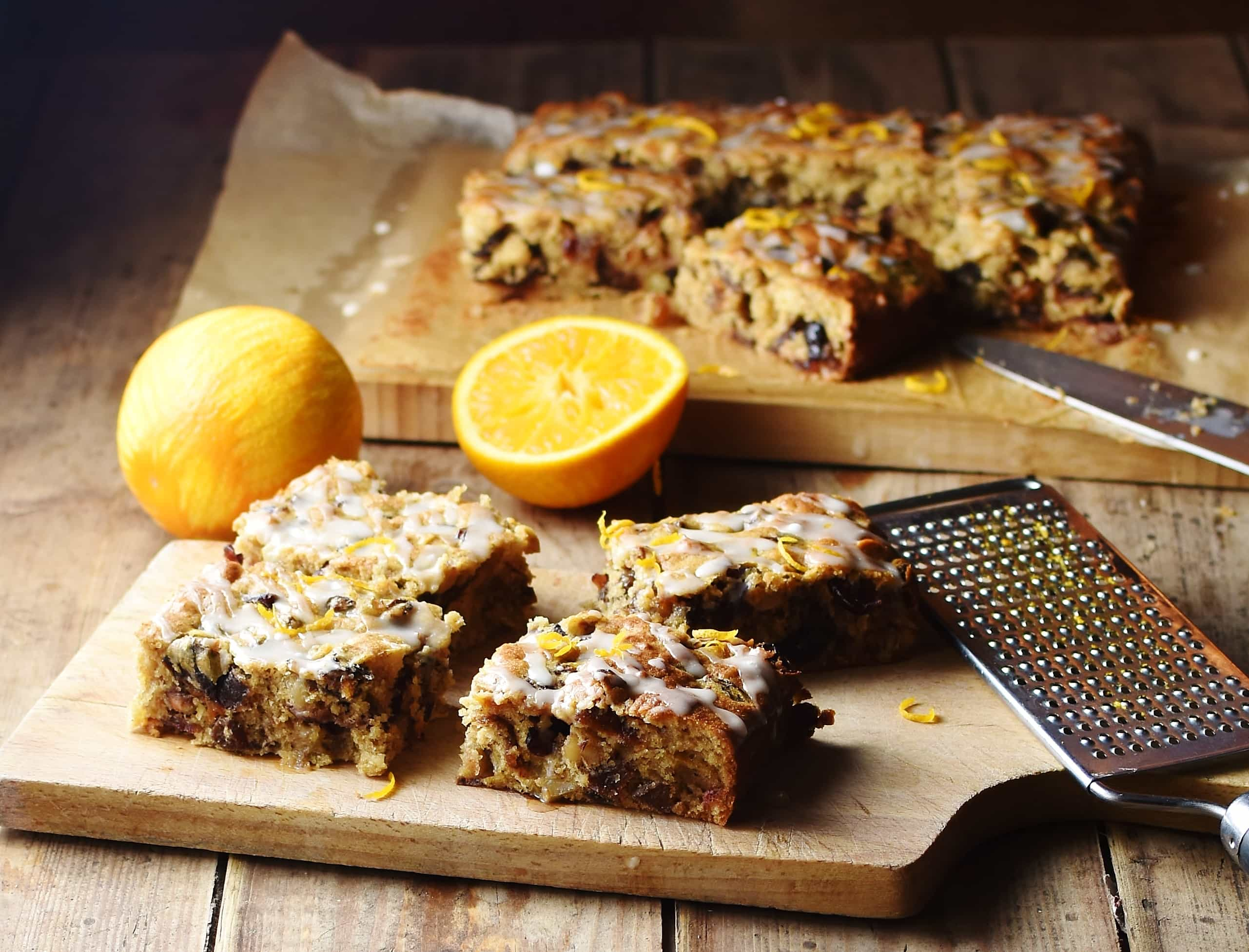Slices of fruit cake on top of wooden board with zester to the right and oranges and more fruit cake in background.