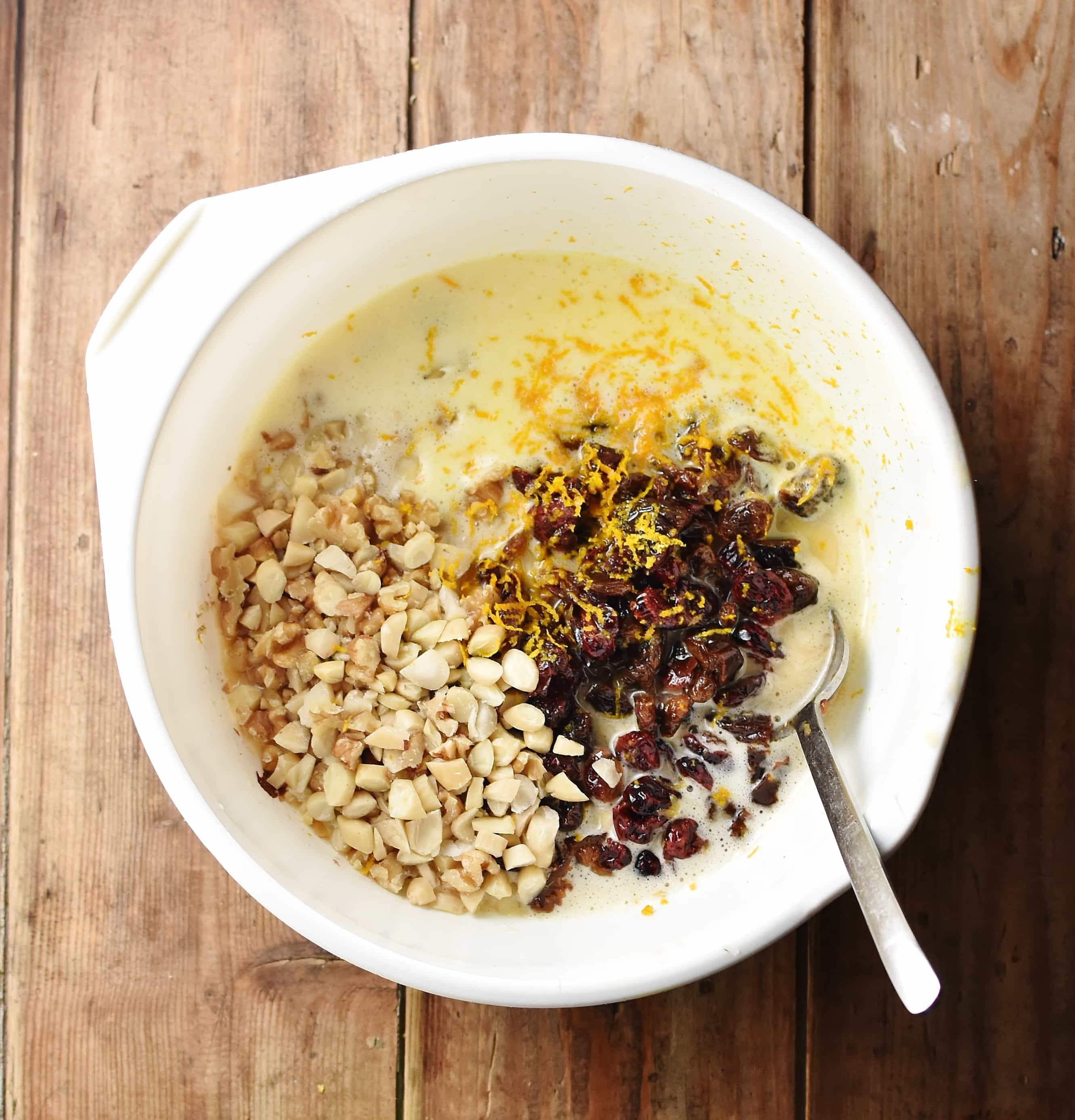 Top down view of nuts, dried fruit, egg mixture and orange zest in large white bowl with spoon.