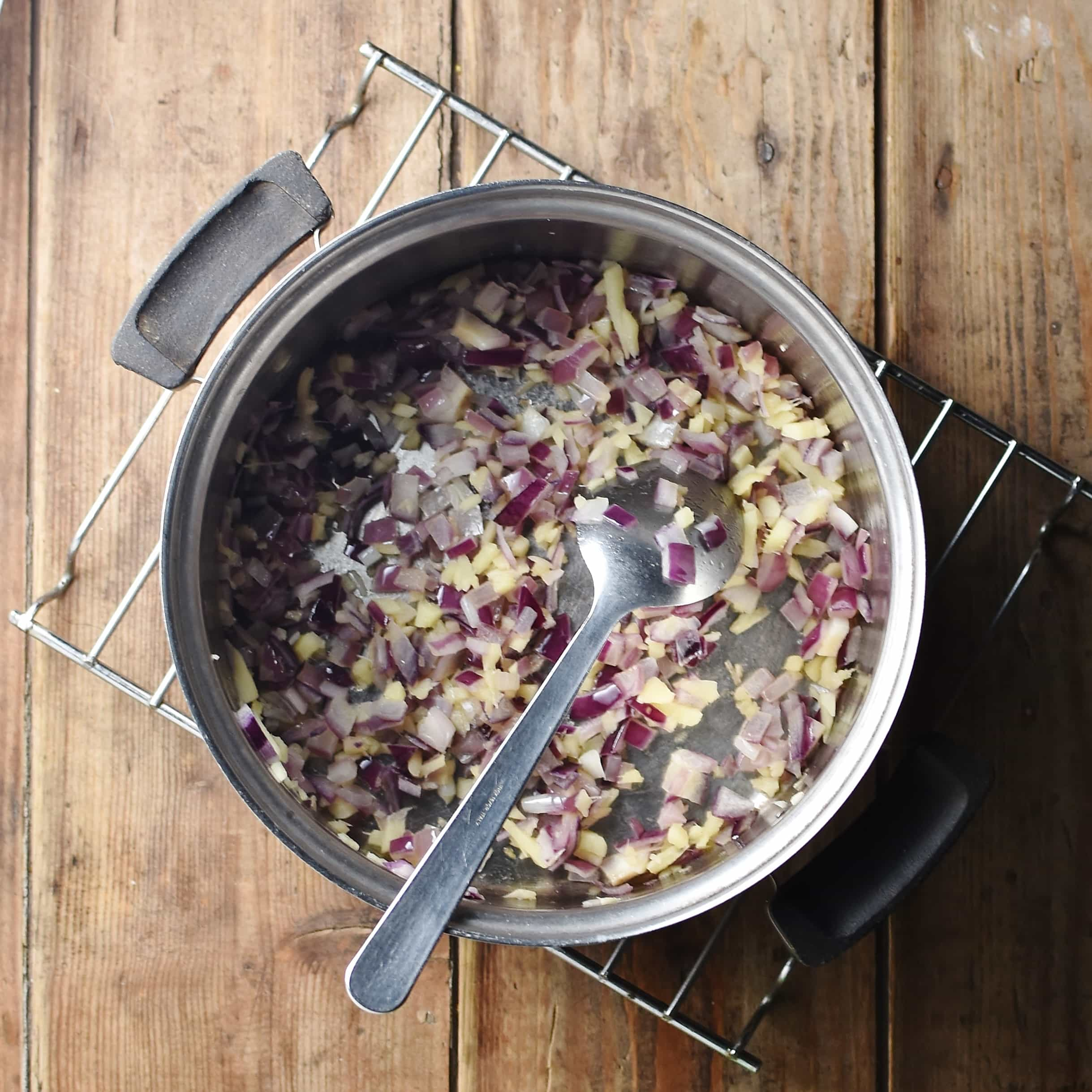 Chopped ginger and red onions in pot with spoon on rack.