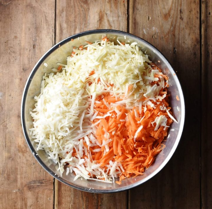 Grated carrot and parsinp in large metal bowl.