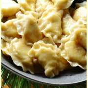 Close-up view of Polish potato and cheese pierogi in black bowl.