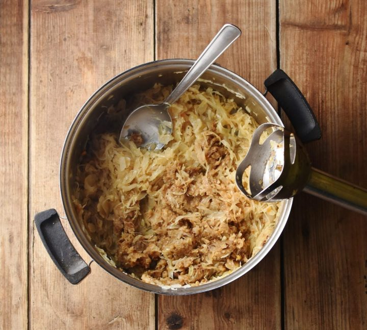 Cooked sauerkraut in pot with spoon and end of hand blender.