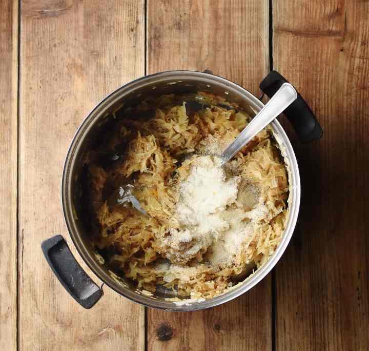 Sauerkraut mixture with breadcrumbs in pot with spoon.
