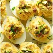 Top down view of smoked salmon deviled eggs garnished with chives and pistachios.