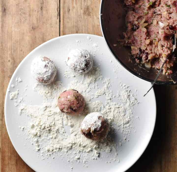 4 turkey stuffing balls coated in flour on large white plate, with stuffing mixture in metal bowl in top right corner.