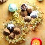 Top down view of chocolate truffles inside 2 glasses wrapped in Christmas decorations.