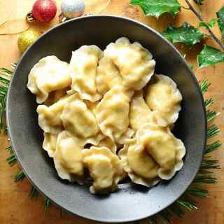 Top down view of Polish potato and cheese pierogi in black bowl on top of wooden table with Christmas decorations.