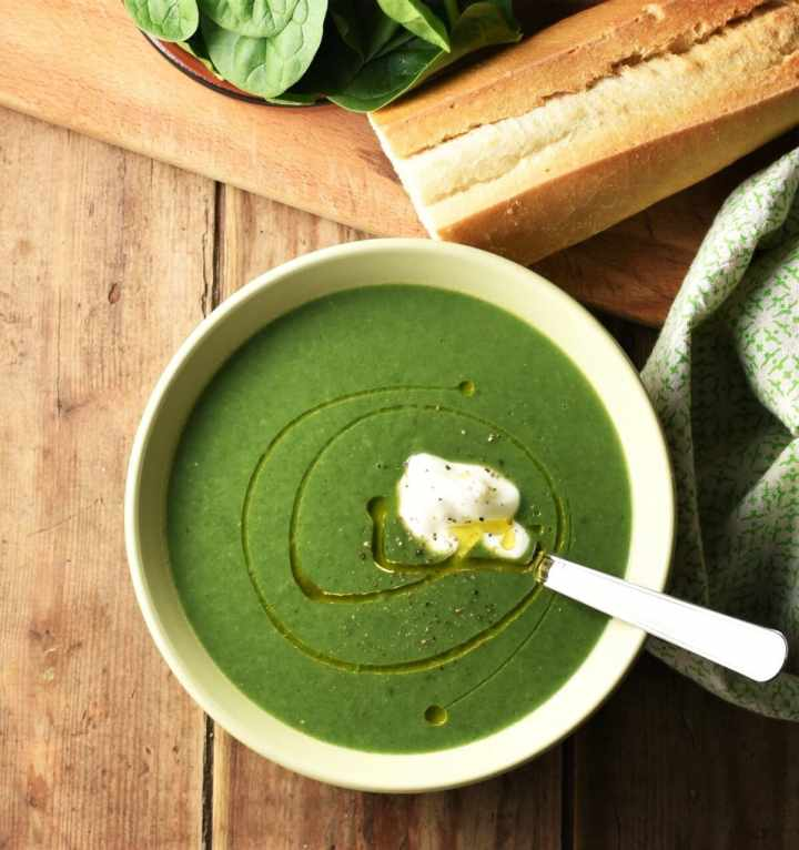 Creamy spinach soup with dollop of yogurt in green bowl with spoon, green cloth, baguette and spinach in background.