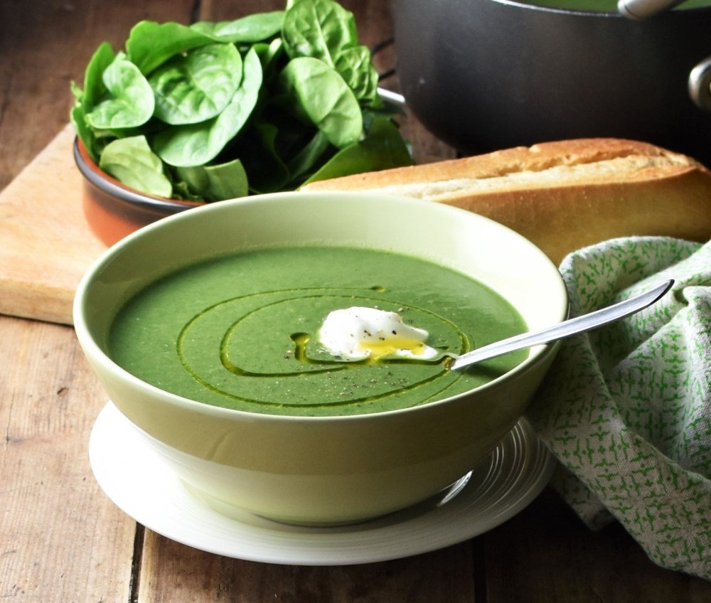 Side view of creamy spinach soup in green bowl with spoon on top of white plate, with spinach, baguette and green cloth in the background.