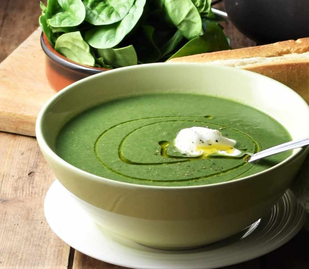 Side view of creamy spinach soup with yogurt in green bowl with spoon on white plate, with spinach in brown dish in background.