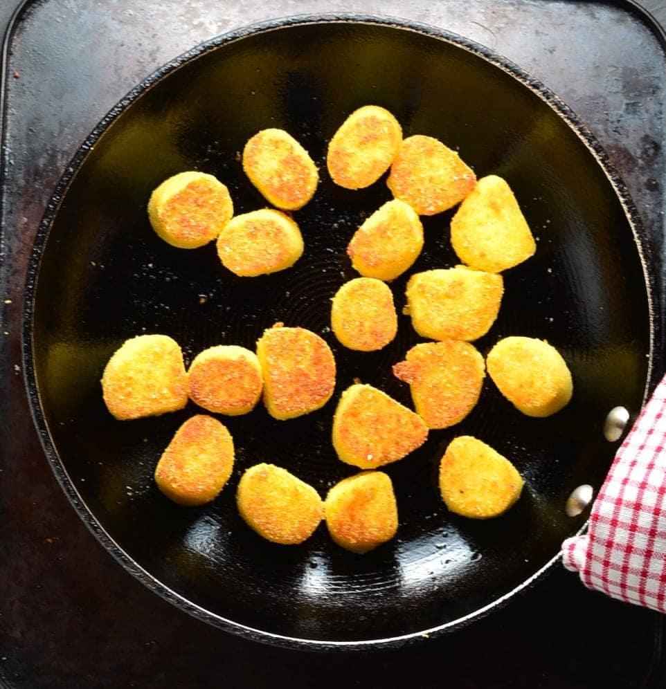 Top down view of potato dumplings with polenta in black skillet.