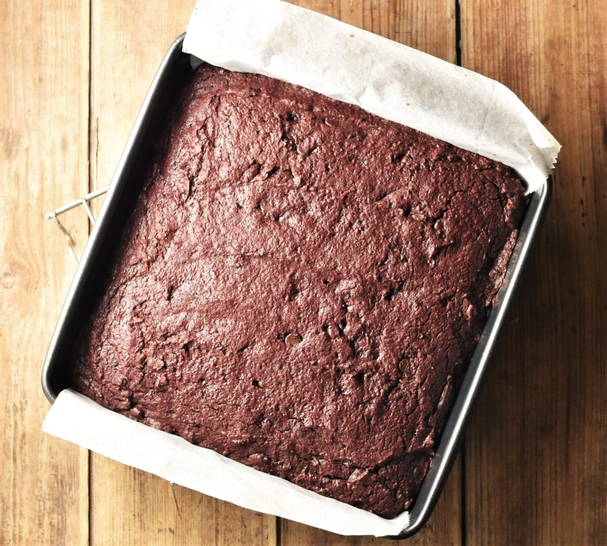 Beet brownie cake in square pan lined with parchment paper.