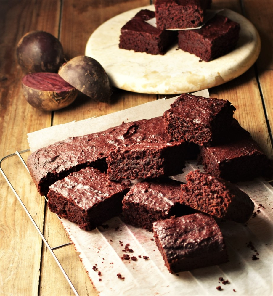 Brownies on top of parchment paper, with raw beets and brownies on marble round plate in background.