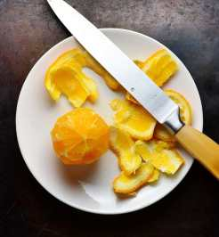 Peeled orange with peel and knife with yellow handle on white plate.