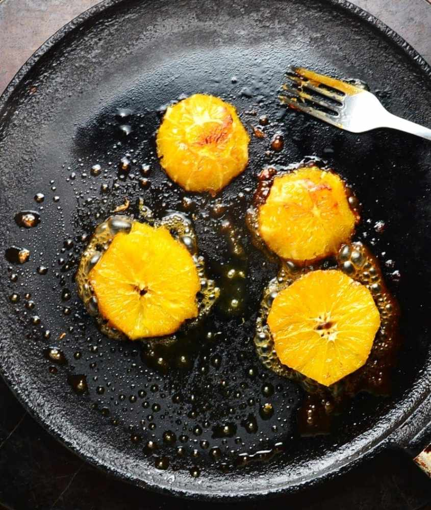 Slices of orange frying in black pan with fork.