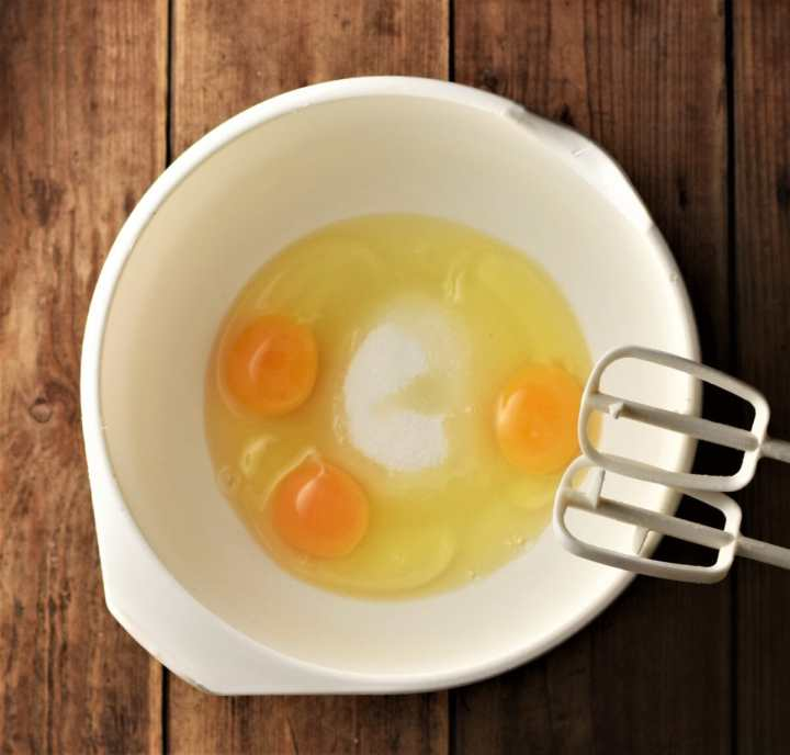 3 eggs and sugar in large white bowl with electric mixer end pieces.