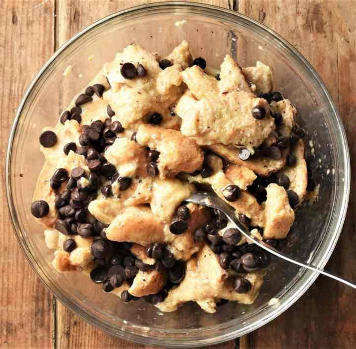 Bread in egg mixture with chocolate chips in mixing bowl.