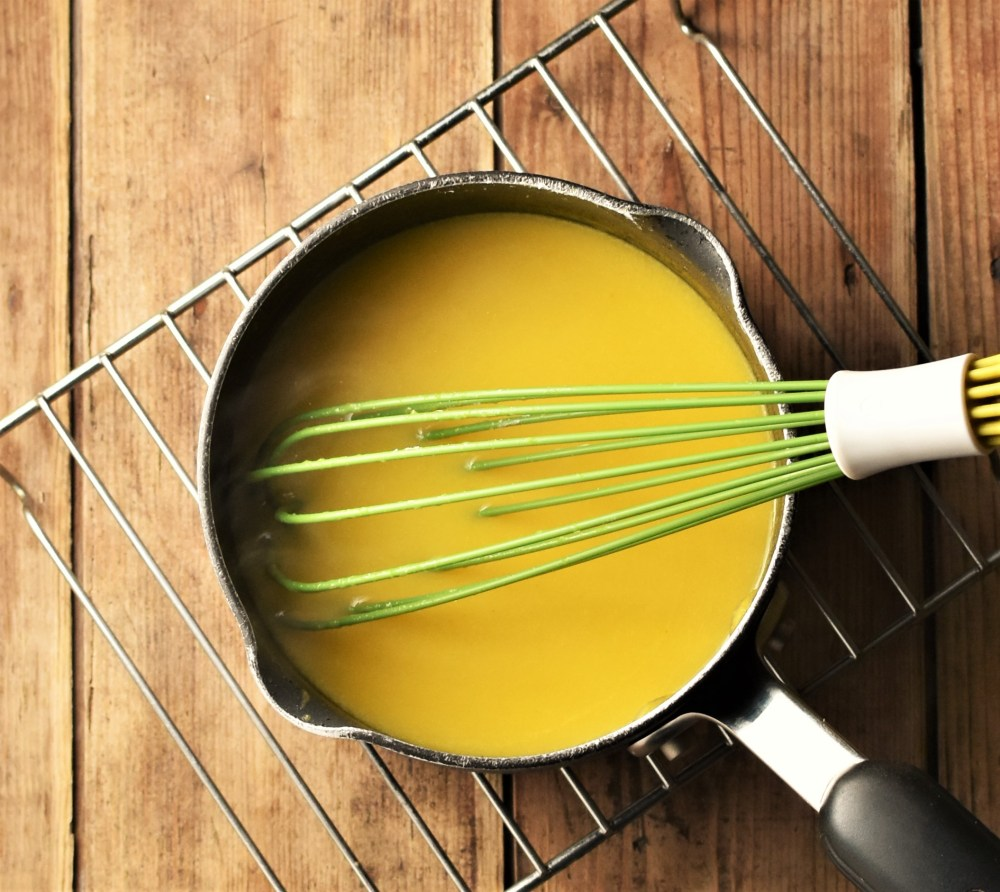 Orange sauce in small pot with green whisk on top of rack.