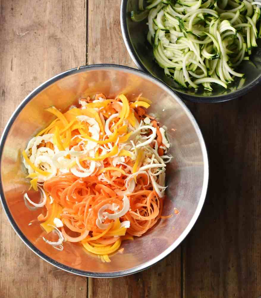 Spiralized vegetables in large metal bowl and zoodles in another bowl in top right corner.