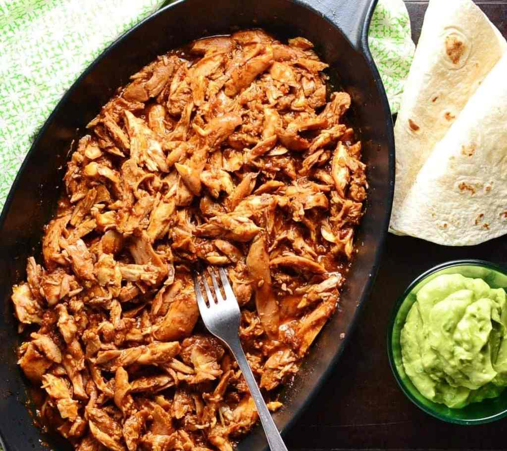 Pulled chicken in black oval cast iron dish with fork, wraps, guacamole in small dish and green cloth.