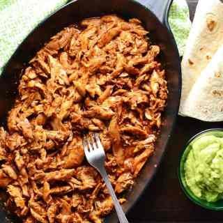 Easy pulled chicken in black oval cast iron dish with fork, wraps, guacamole in small dish and green cloth.