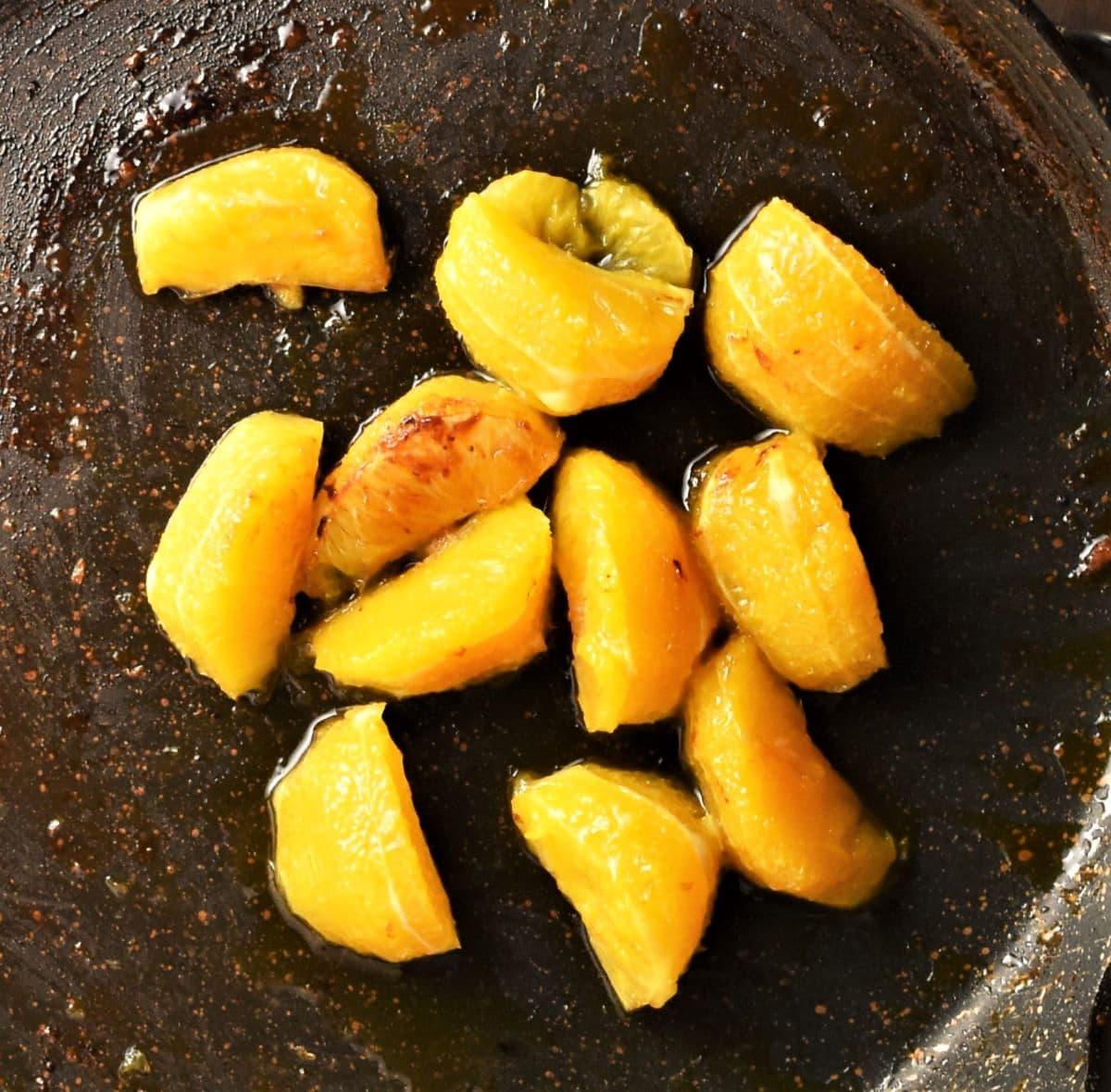 Frying peeled orange wedges in pan.