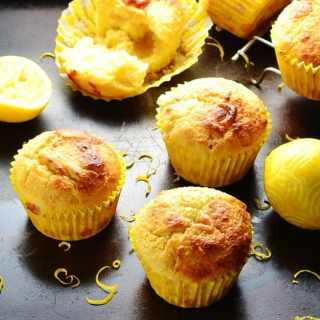 Lemon marzipan muffins with lemon and zest on dark brown tray.
