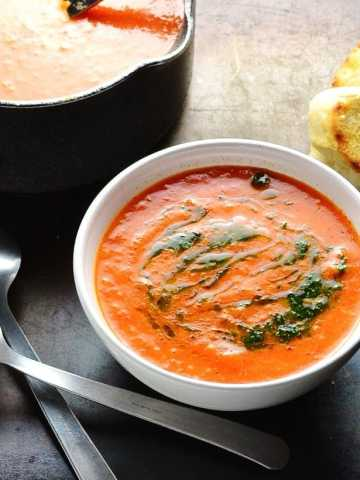 Red pepper and tomato soup with basil drizzle in white bowl and black saucepan in top left corner, toasted baguette slices and spoons on black table.