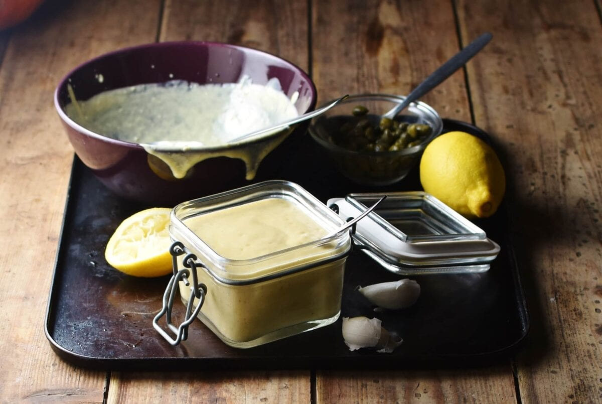 Caesar salad dressing in square open jar with spoon, lemon, dressing in purple bowl and capers in small dish with spoon in background.