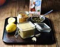 Dressing in square open jar with spoon, lemon, miso paste in jar, capers in small dish with spoon and silken tofu package in background.