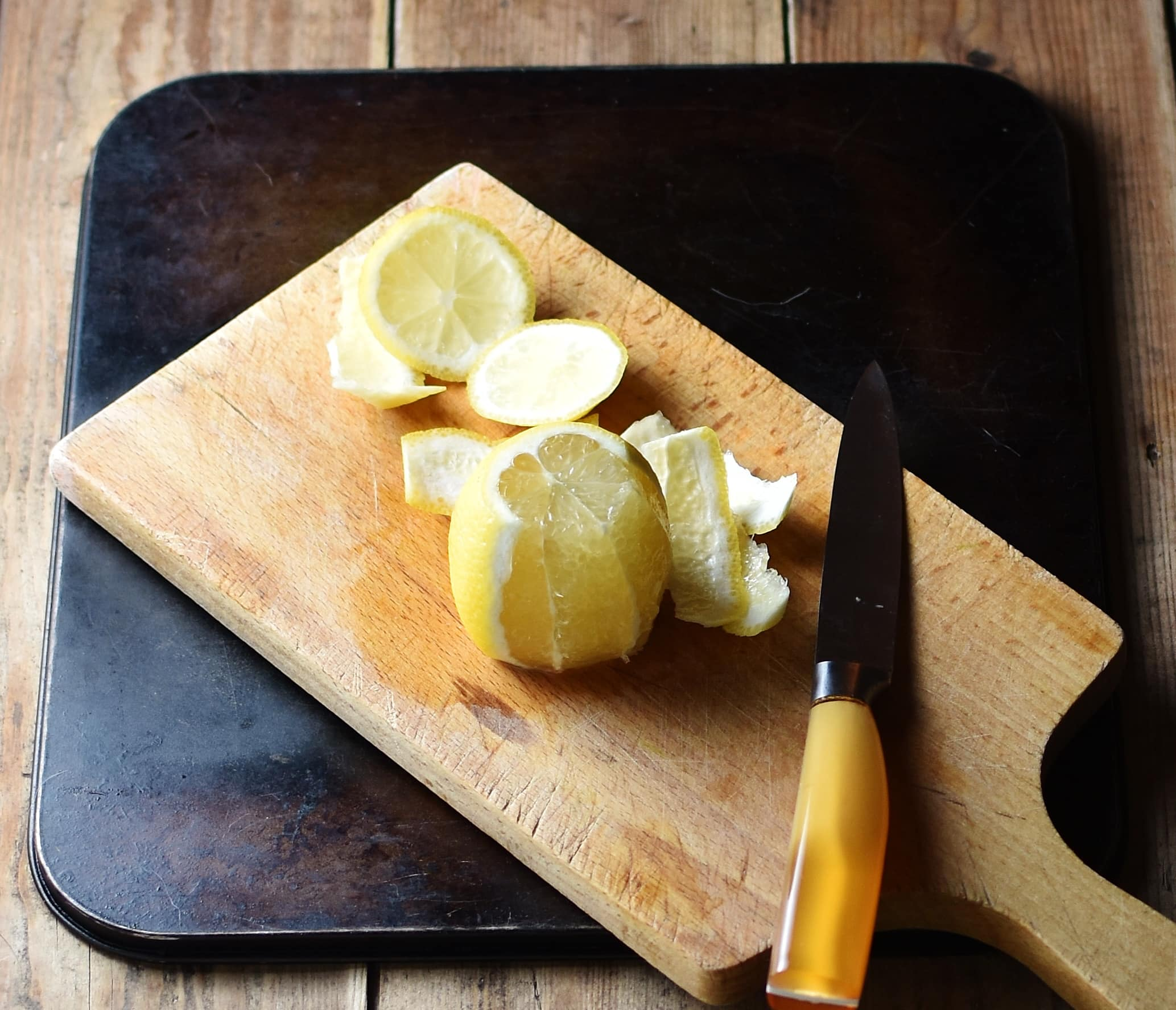 Lemon and peel with knife on top of cutting board.