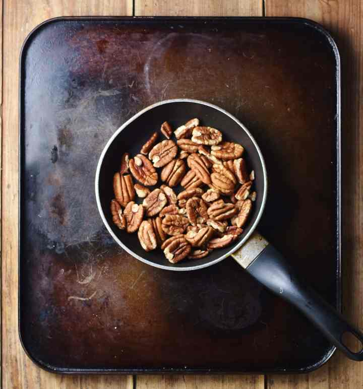 Top down view of pecans in small pan.