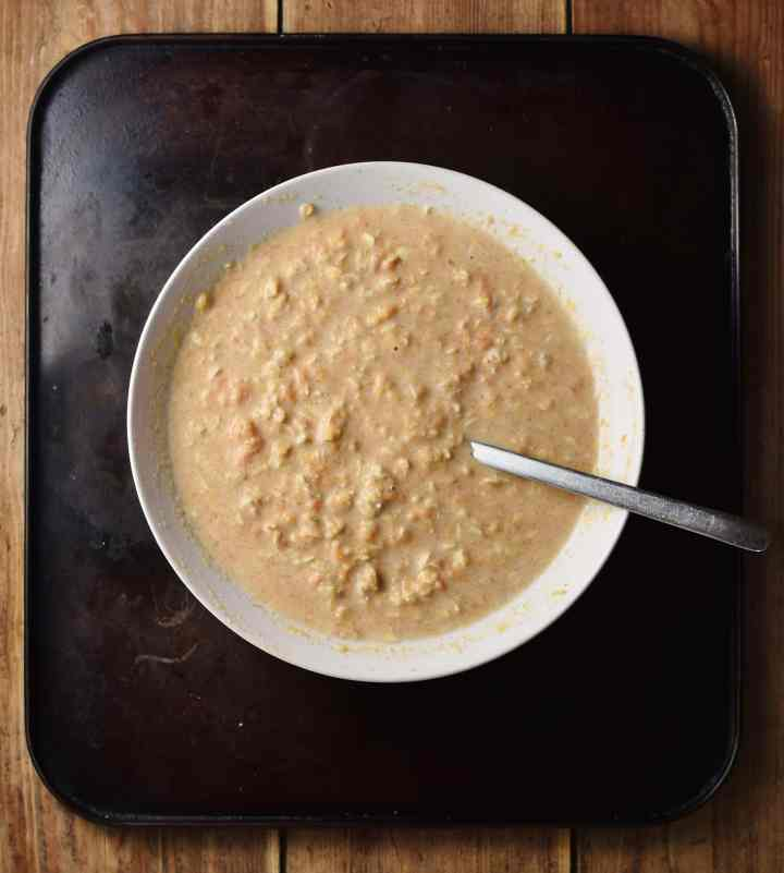 Top down view of overnight oats in white bowl with spoon.