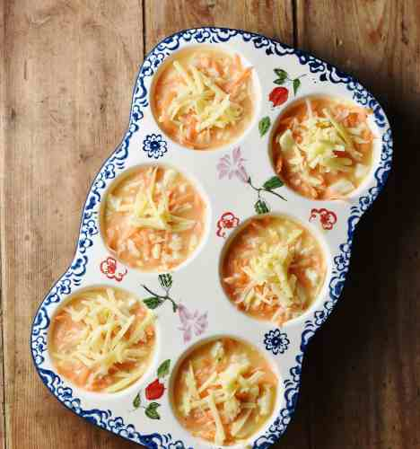 Sweet potato and egg mixture in 6-hole ceramic muffin pan with blue flower pattern.