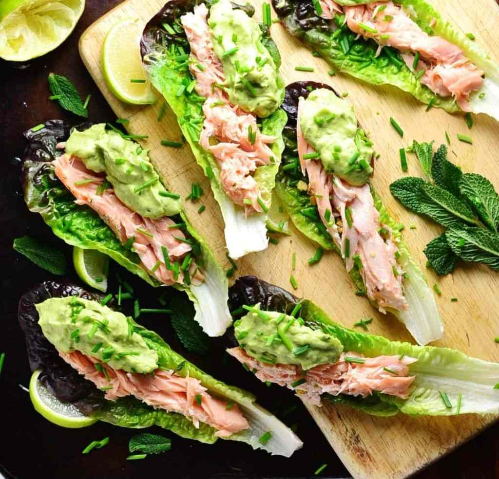 Top down view of lettuce wraps with salmon and avocado sauce with lime wedges and garnish of herbs on top of wooden board and dark table.