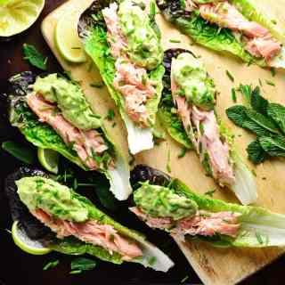 Top down view of lettuce wraps with salmon and guacamole with garnish of herbs on top of wooden board and dark table.