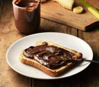 Side view of toast with chocolate hazelnut spread and knife on white plate, with spread in cup and cutting board in background.