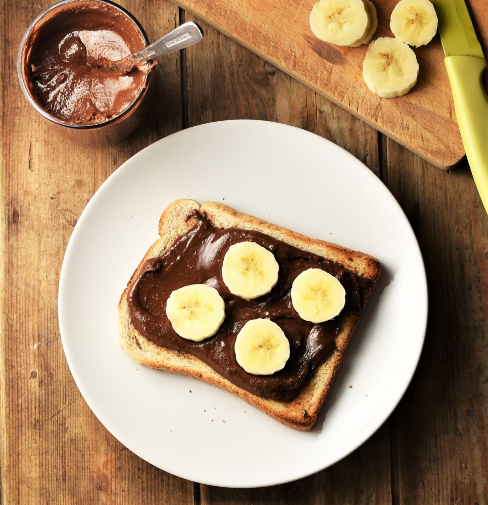 Top down view of hazelnut cacao spread on toast with sliced banana on white plate, with spread in cup and banana in background.