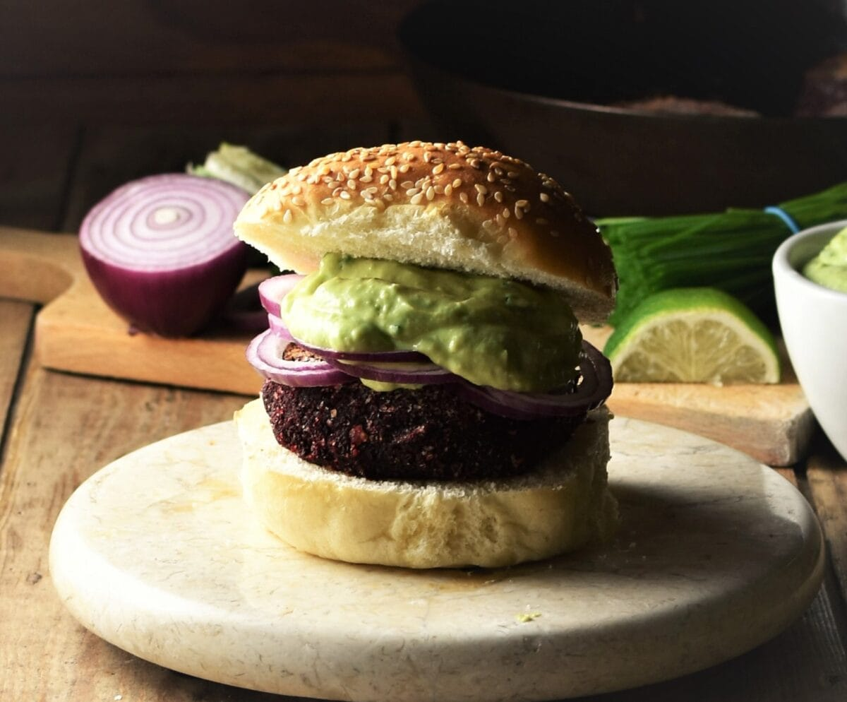 Side view of beet burger on top of marble plate with red onion and lime in background.