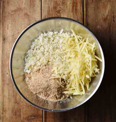 Cauliflower rice, grated cheese and breadcrumbs in large metal bowl.