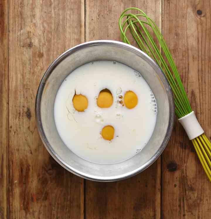 4 eggs with milk inside metal bowl with green whisk to the right.