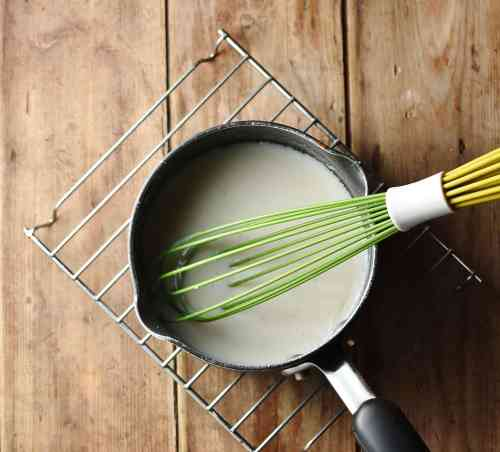 White sauce in small saucepan with green whisk on top of cooling rack.